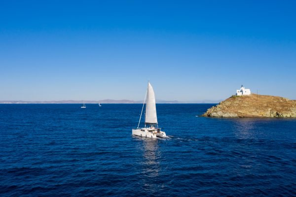 Sailing. Sailboat catamaran with white sails, rippled sea background, Lighthouse on a cape. Greece, Kea Tzia island. Summer holidays in Aegean sea. Aerial drone view